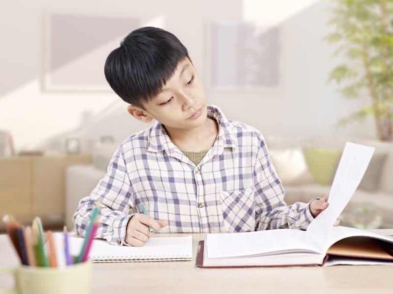 Aziatische schooljongen die thuis bestuderen stock foto