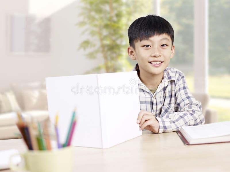 Aziatische schooljongen die thuis bestuderen stock fotografie