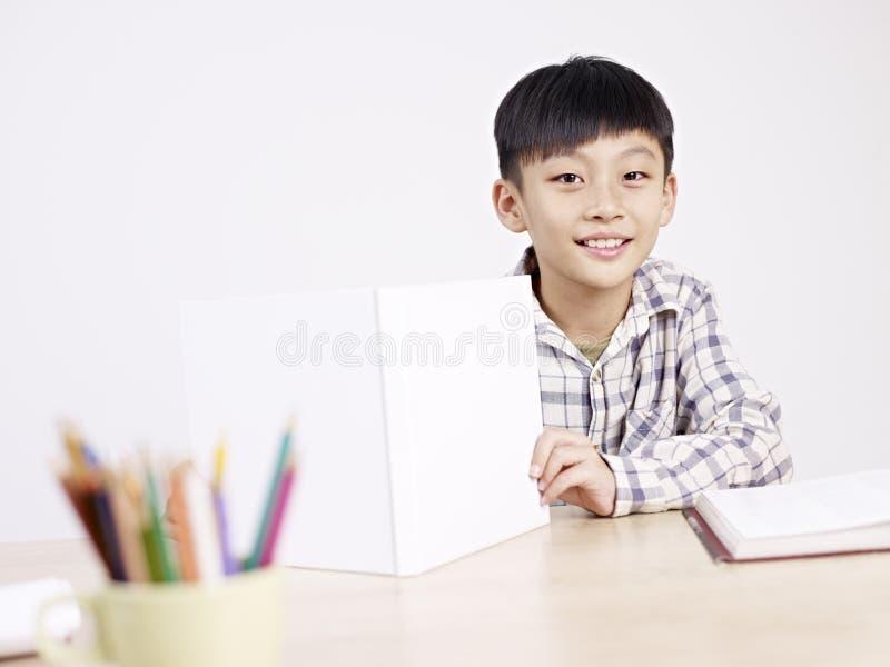 Aziatische schooljongen die thuis bestuderen stock afbeelding