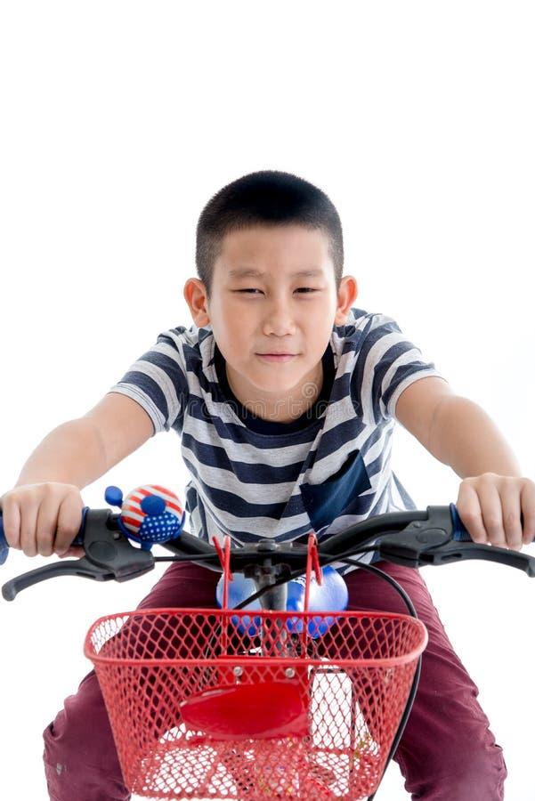 Aziatische schooljongen met rugzak die een fiets berijden stock foto