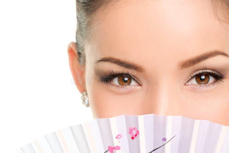 Aziatische schoonheidsogen - make-upvrouw die met ventilator kijken stock fotografie