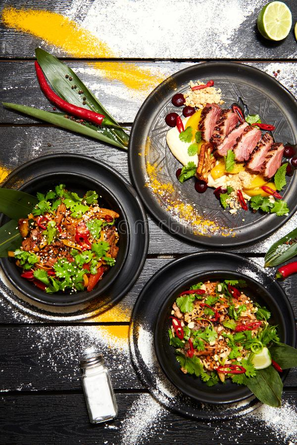 Aziatische schotels op een zwarte lijst De eendborst met perzik, noedels met rundvlees, vult Thai met kip en garnalen op stock afbeelding
