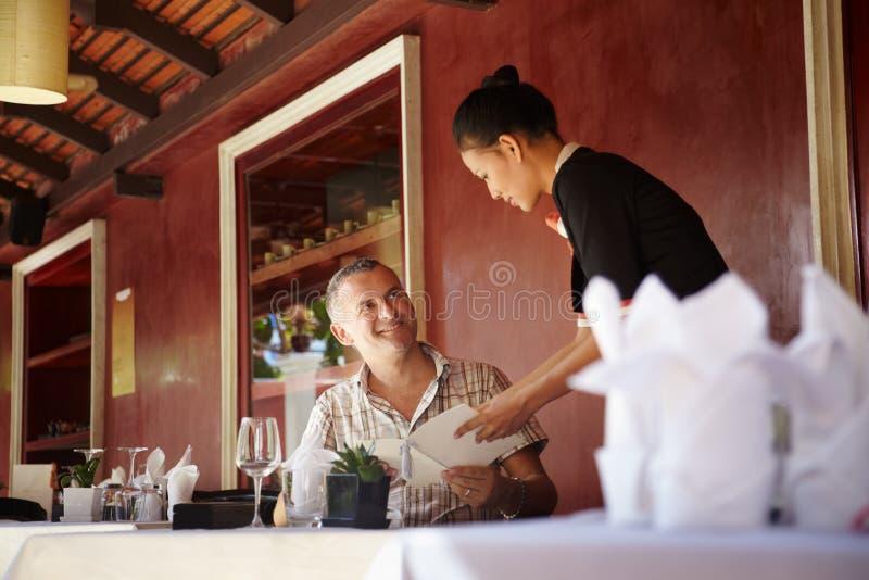 Aziatische serveerster die met cliënt in restaurant spreekt stock afbeelding