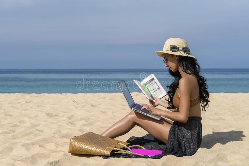 Aziatische sexy vrouw in bikini, gebruikend laptop computer en houdend boek op een strand, reis van de zomervakantie Freelance he royalty-vrije stock fotografie