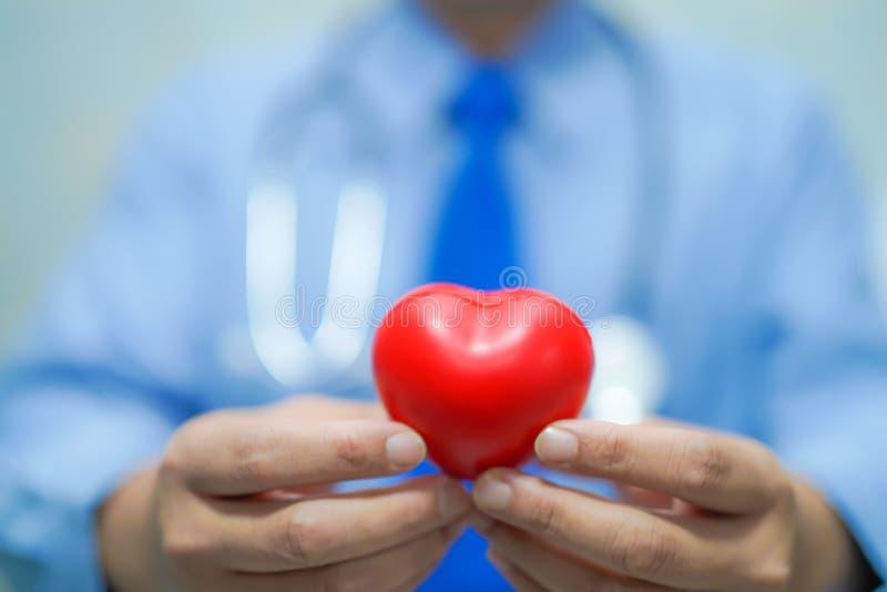 Aziatische slimme mens arts die een rood hart houden: gezond sterk medisch concept stock foto's
