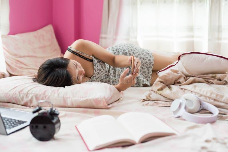 Aziatische smartphone van het meisjesspel op bed stock afbeelding