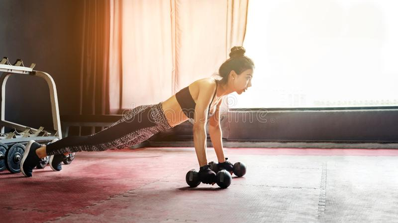 Aziatische sportenvrouw die oefeningen met domoor en opdrukoefeningen doen bij royalty-vrije stock foto