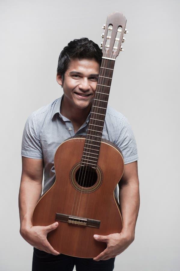 Aziatische Student die een gitaar houdt stock afbeeldingen