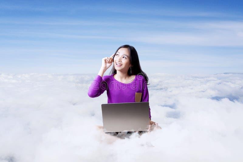 Aziatische student die met computerlaptop werken bovenop wolken royalty-vrije stock afbeeldingen
