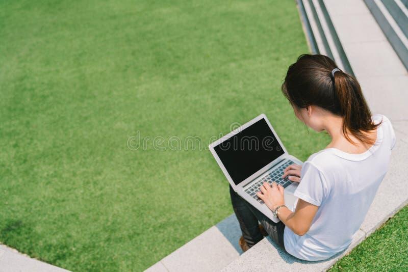 Aziatische student of freelance vrouw die laptop op treden in universitaire campus of modern park met behulp van royalty-vrije stock afbeeldingen