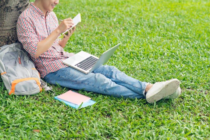 Aziatische student het schrijven samenstellingen in voorbeeldenboeken die op park zitten stock fotografie