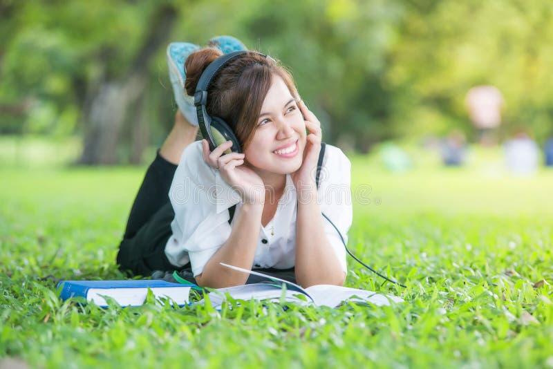Aziatische student met Hoofdtelefoons in openlucht Het genieten van van muziek royalty-vrije stock foto