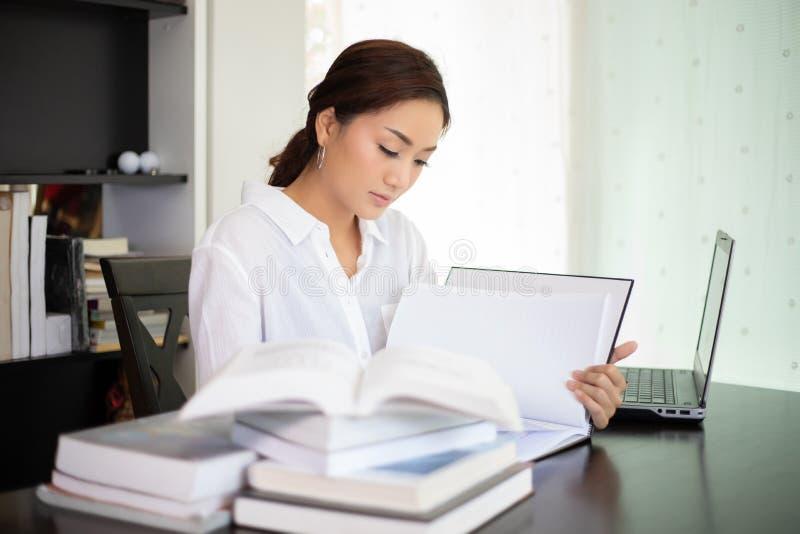 Aziatische studente die en een boek voor ontspanning glimlachen lezen royalty-vrije stock afbeeldingen