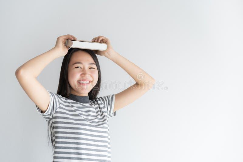 Aziatische studente die van universiteit zich op een witte achtergrond bevinden die een boek op vrouwenhoofd houden De vrouwen di stock foto