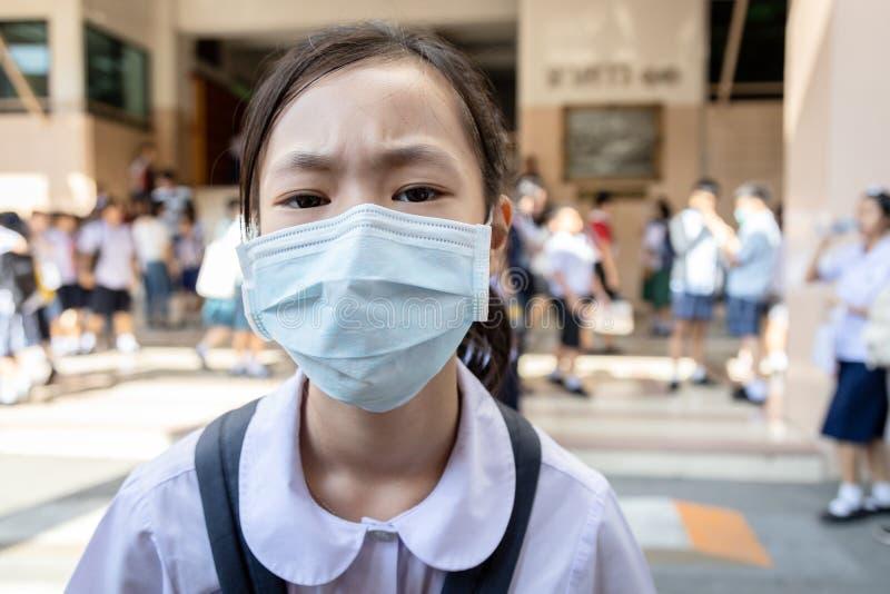 Aziatische studente van een meisje met een beschermende medische gezichtsmasker op school, epidemie, verspreiding van Coronavirus royalty-vrije stock afbeeldingen