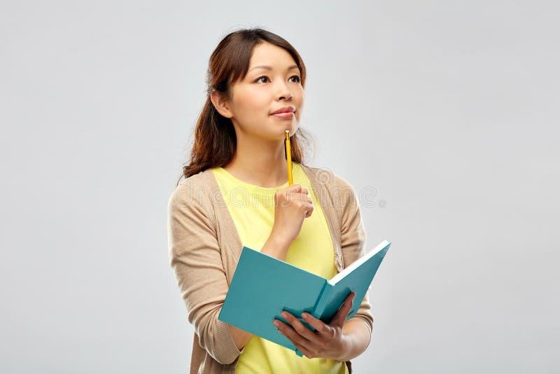 Aziatische studentenvrouw met agenda en potlood royalty-vrije stock fotografie