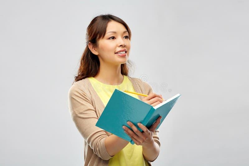 Aziatische studentenvrouw met agenda en potlood stock afbeelding