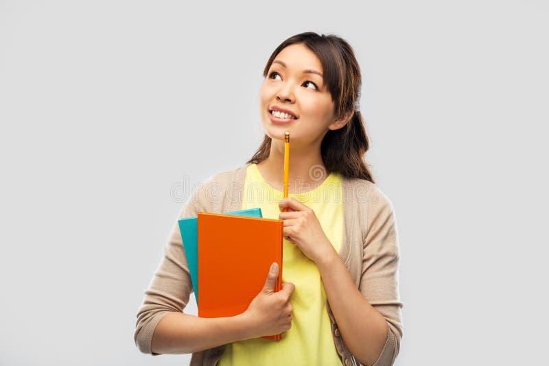 Aziatische studentenvrouw met boeken en potlood stock afbeeldingen
