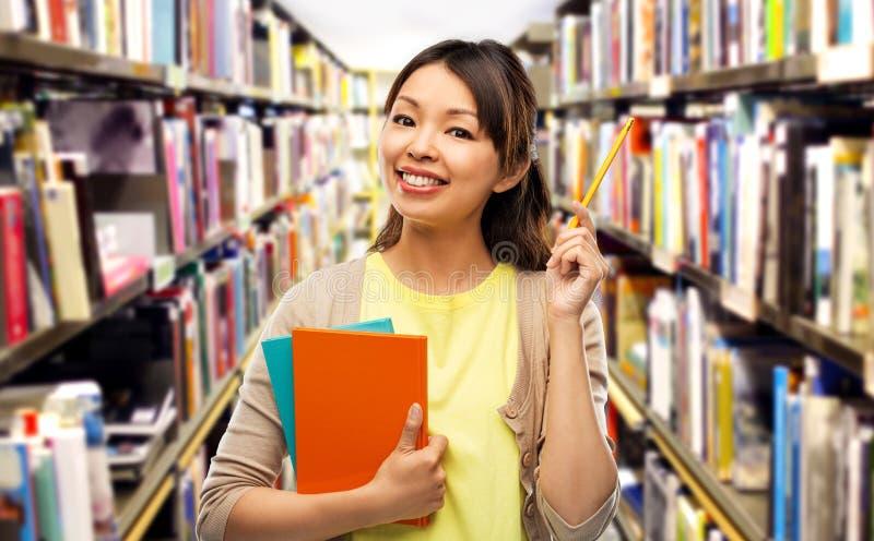 Aziatische studentenvrouw met boeken en potlood stock foto