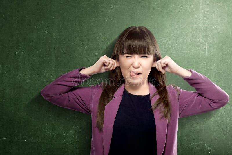 Aziatische studentenvrouw met grappige uitdrukking die zich met bordachtergrond bevinden royalty-vrije stock foto