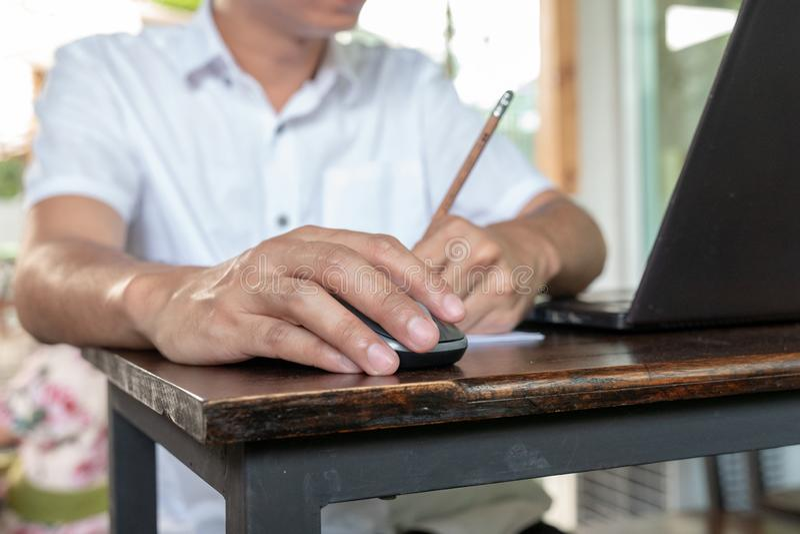 Aziatische tan huid die draadloze muis op de uitstekende houten lijst houden en potlood met zijn linkerhand schrijven stock afbeeldingen