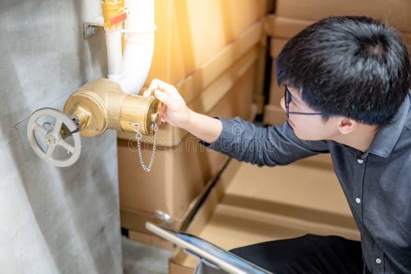 Aziatische technicus die de klep van de waterpoort controleren stock fotografie