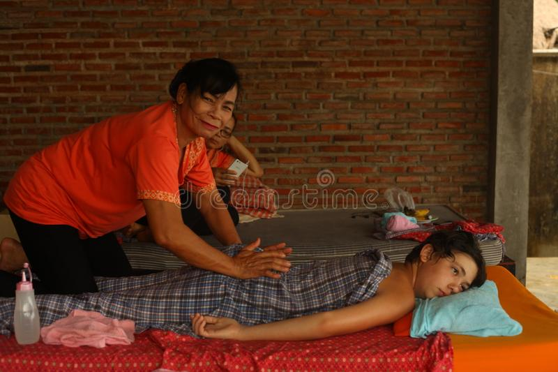 Aziatische Thaise vrouw die massage uitvoeren aan Europese tienerjongen royalty-vrije stock fotografie