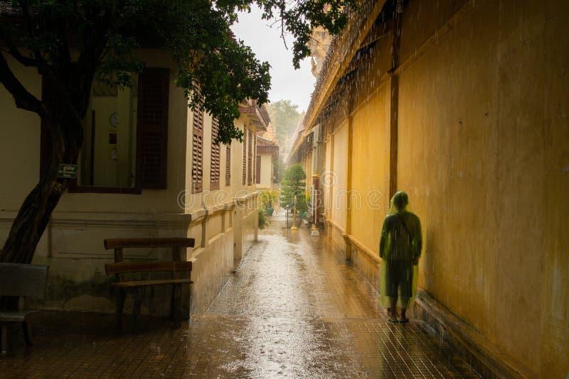 Aziatische tiener die op de tegen te houden moessonregen wachten stock afbeeldingen