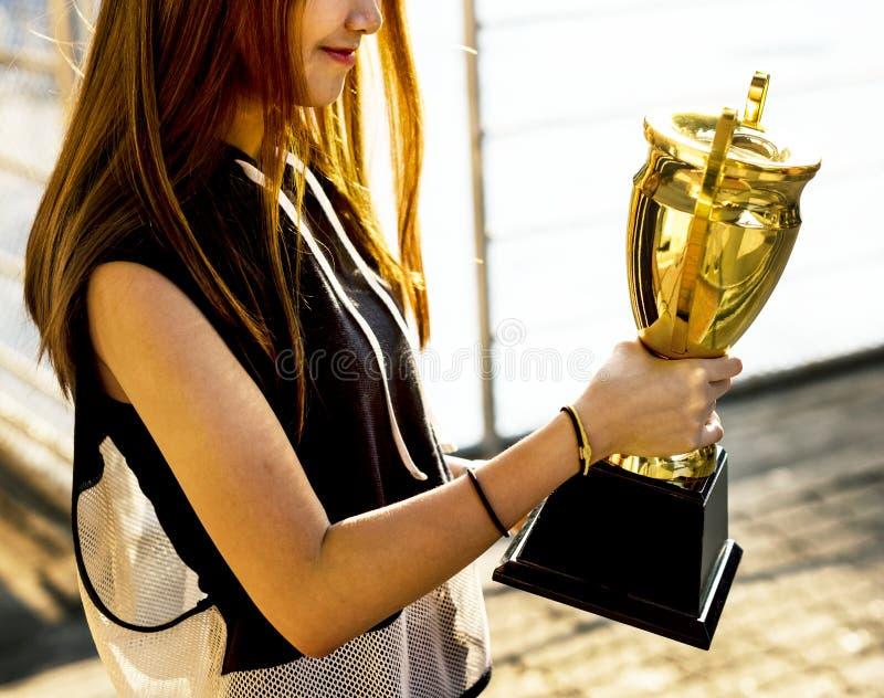 Aziatische tiener die in sportieve kleren een trofee in openlucht houden royalty-vrije stock foto's