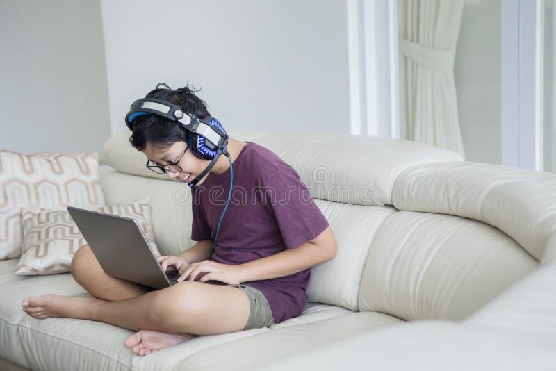 Aziatische tienerjongen die laptop op de bank met behulp van royalty-vrije stock afbeelding