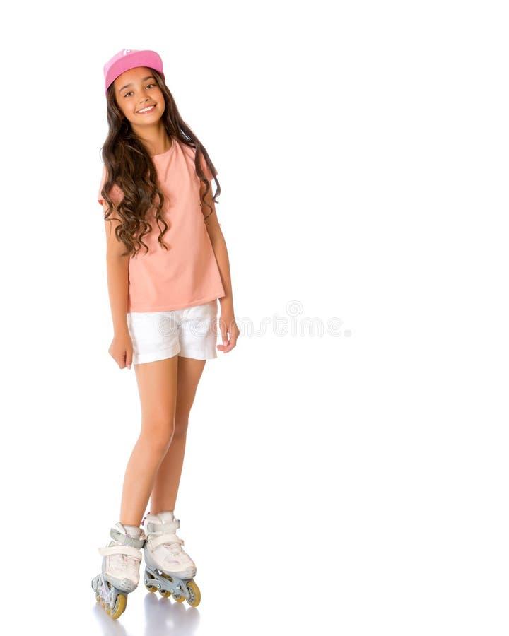 Aziatische tienermeisje rol-schaatst stock foto's