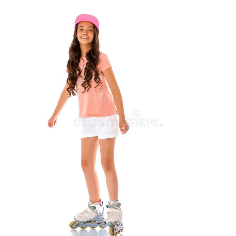 Aziatische tienermeisje rol-schaatst stock foto