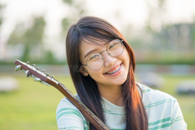 Aziatische tienermeisjes met een gitaar bij de schouder in het gazon Zij draagt steunen en slijtageoogglazen stock fotografie