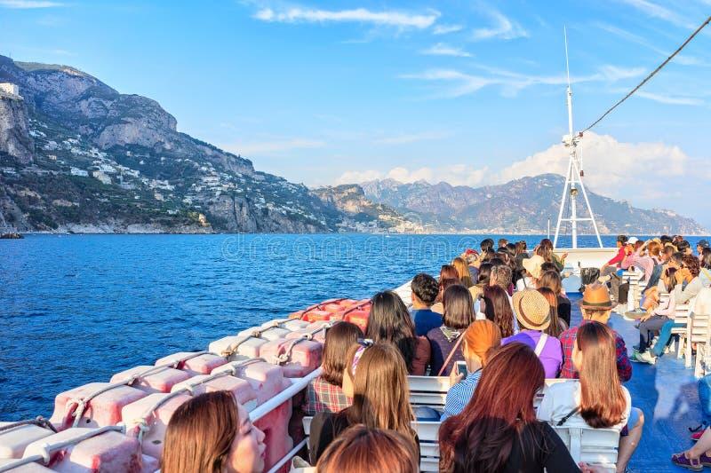 Aziatische Toeristen aan boord van excursieboot in Thyrreense Zee in Positano stock fotografie
