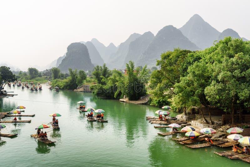 Aziatische toeristen die door bamboevlotten reizen langs de Yulong-Rivier royalty-vrije stock afbeelding