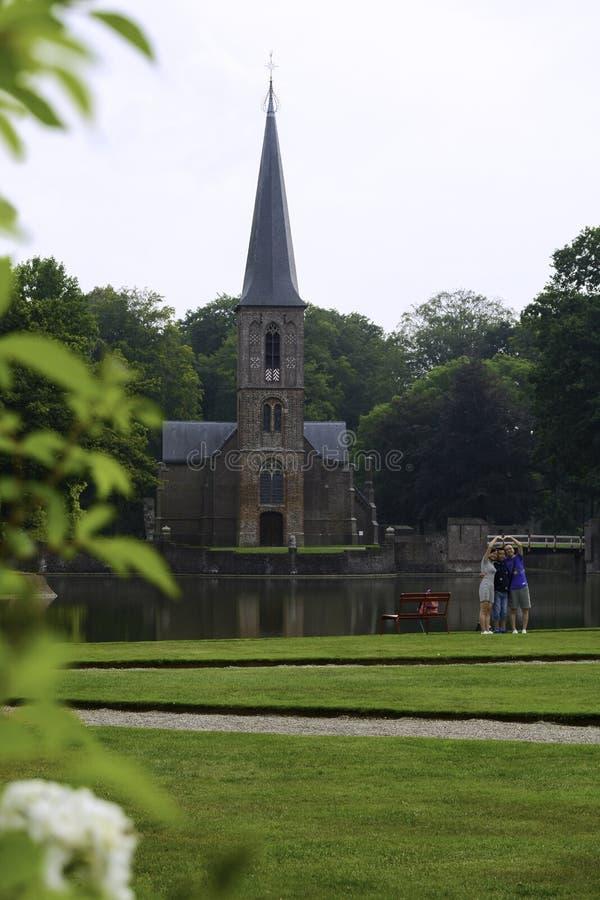 Aziatische toeristen stellen zich voor een kerk voor en maken een zelfingenomen foto stock fotografie
