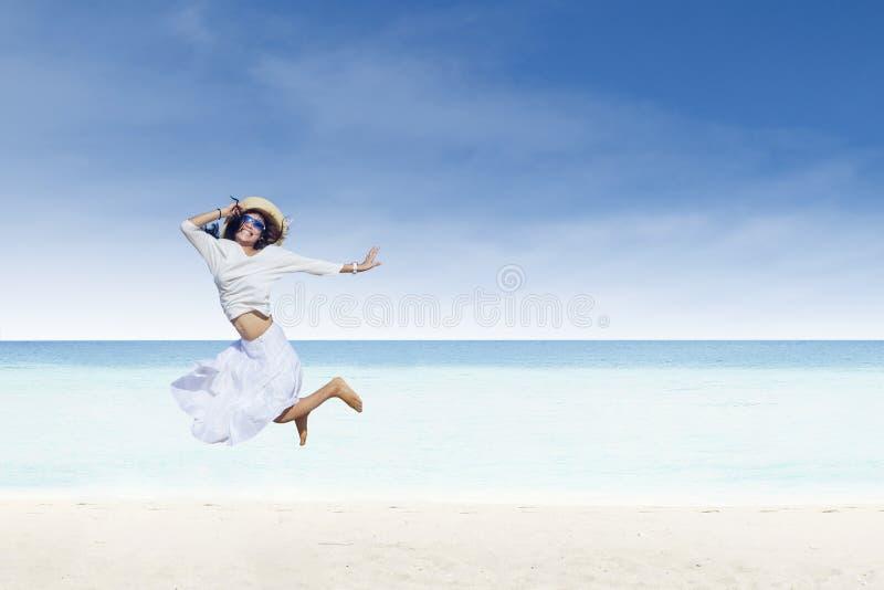 Aziatische toeristensprong bij wit zandstrand stock foto's