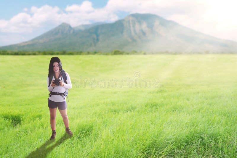 Aziatische toeristenvrouw die op een sleep van de groenheuvel met rugzak en camera lopen stock fotografie