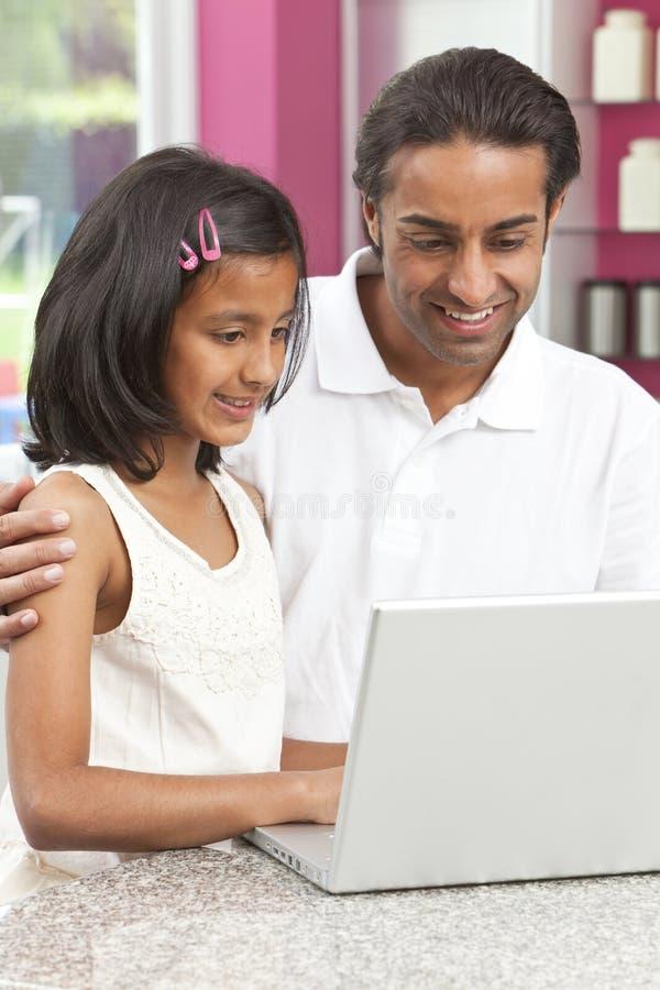 Aziatische Vader & Dochter die Laptop thuis met behulp van stock fotografie