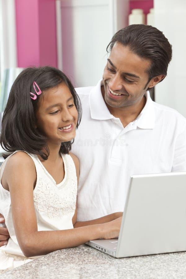Aziatische Vader & Dochter die Laptop thuis met behulp van stock foto's