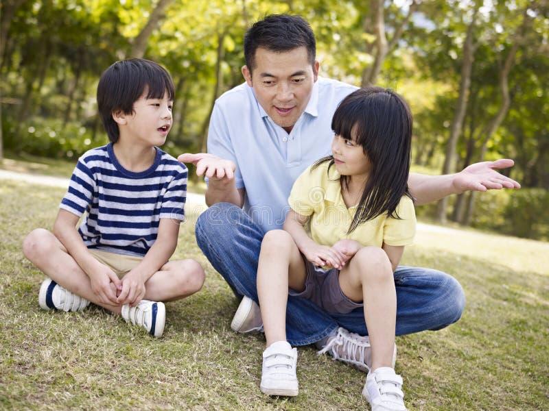 Aziatische vader en kinderen die in park spreken stock fotografie