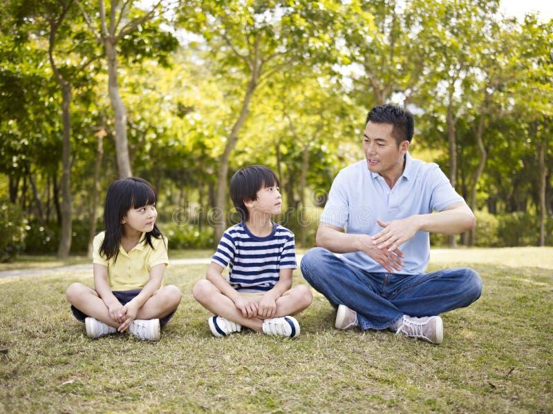 Aziatische vader en kinderen die in park spreken royalty-vrije stock foto's