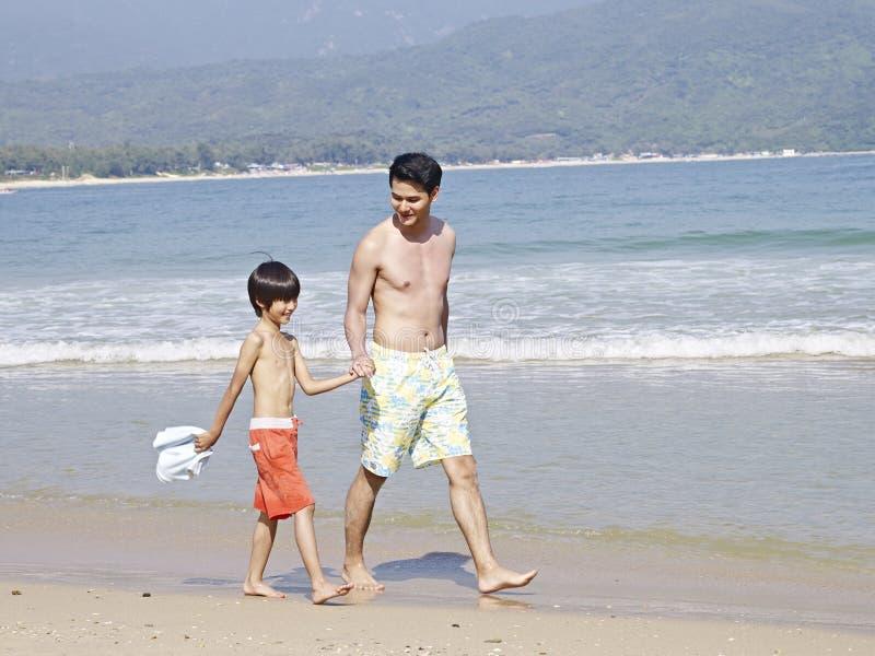 Aziatische vader en zoon die op strand lopen stock fotografie