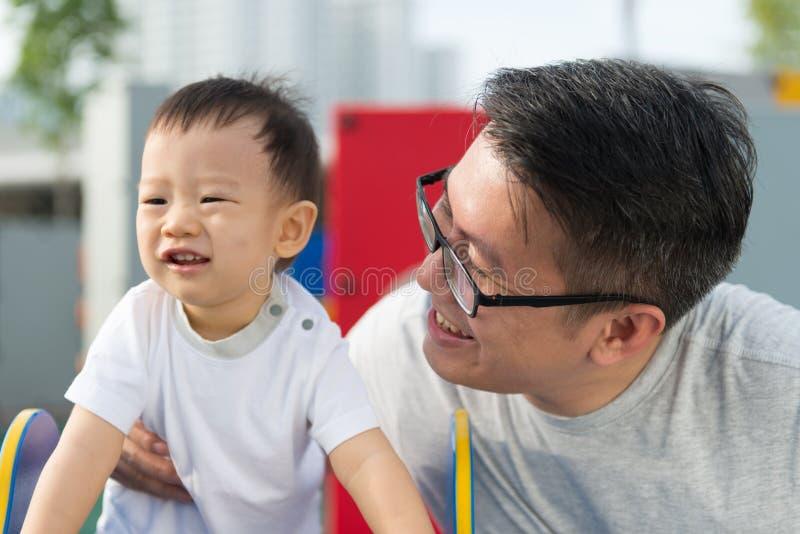 Aziatische vader met zijn kleine jongen bij speelplaats royalty-vrije stock foto's