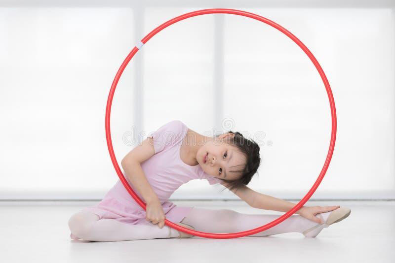 Aziatische van de meisjeszitting en holding gymnastiek- hoepel royalty-vrije stock afbeeldingen