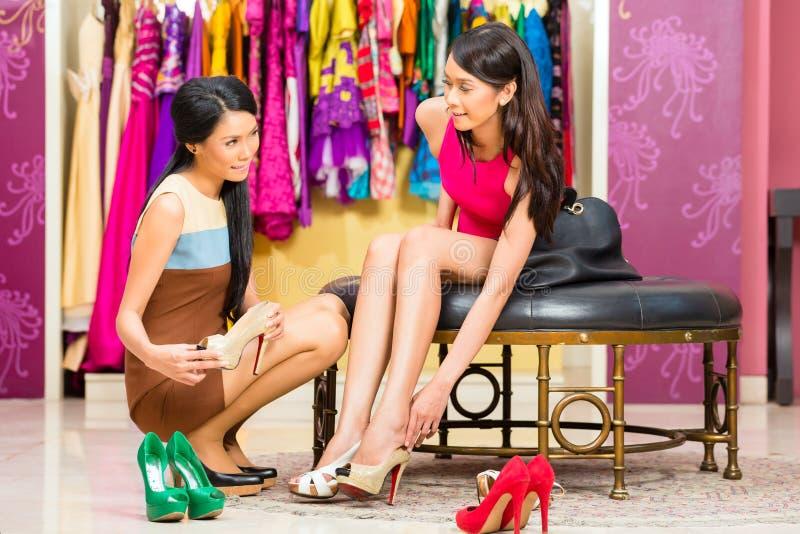 Aziatische verkoopdame in winkel die schoenen aanbieden stock fotografie
