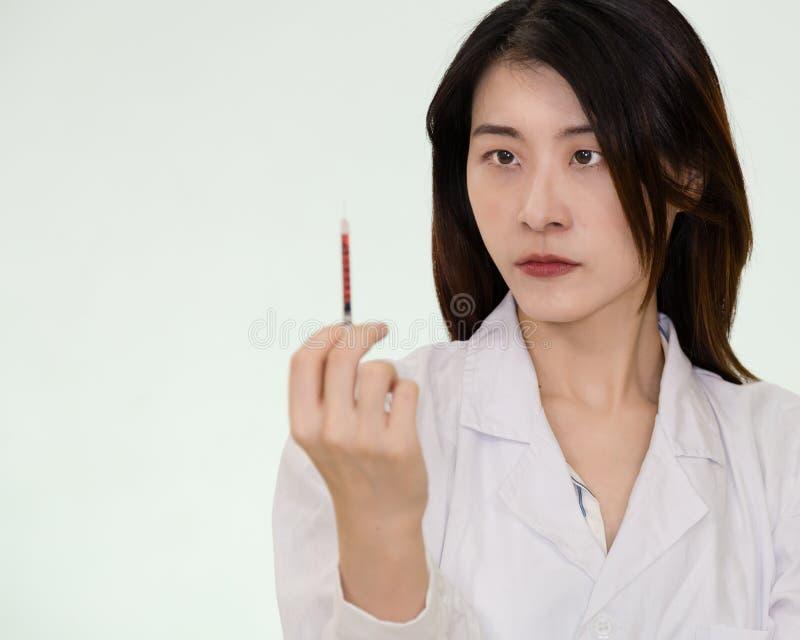 Aziatische verpleegster met bloed-gevulde spuit stock fotografie