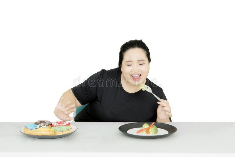 Aziatische vette vrouw die gezond voedsel op studio eten royalty-vrije stock afbeelding