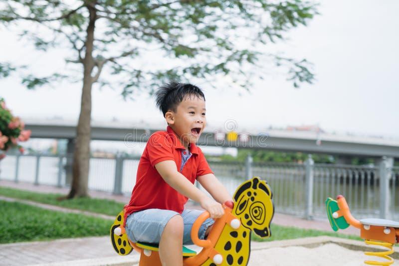 Aziatische Vietnamese knappe jongenszitting op geschommel bij openluchtspeelplaats royalty-vrije stock foto