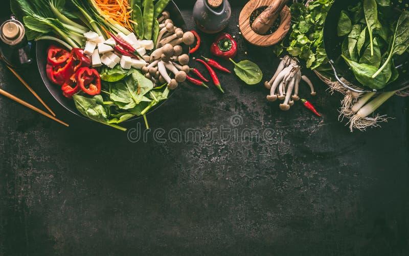 Aziatische voedselachtergrond Wokpan met vegetarische ingrediënten: groenten en tofu op keukenlijst met eetstokjes, kruiden en kr stock foto's